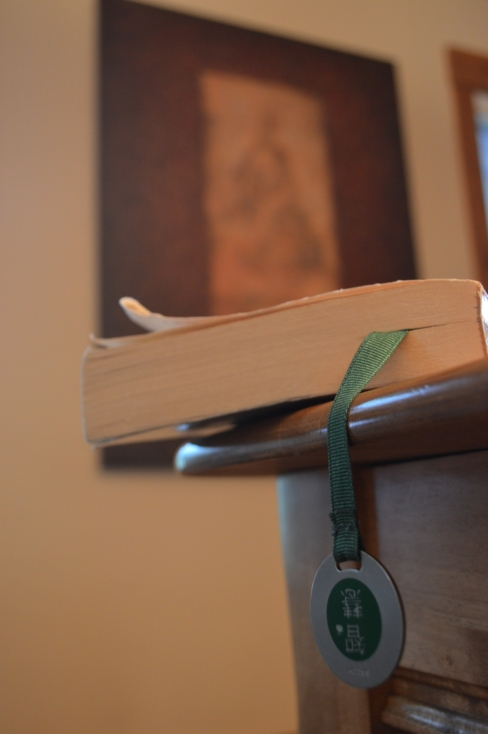 A book dangling off the edge of a table, closed with a page marked. There
